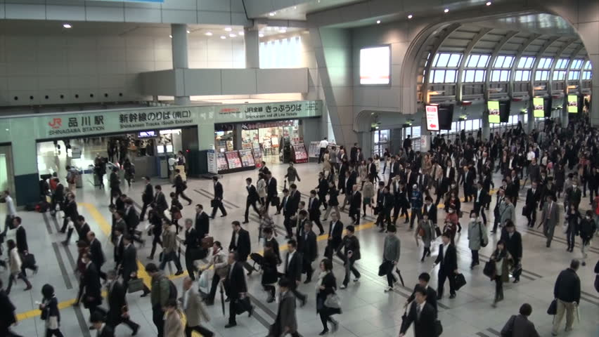 TOKYO, JAPAN - 6 NOVEMBER 2012: Beautiful overview of commuters exiting the platforms and walking into the main building of the Shinagawa train station in Tokyo, Japan