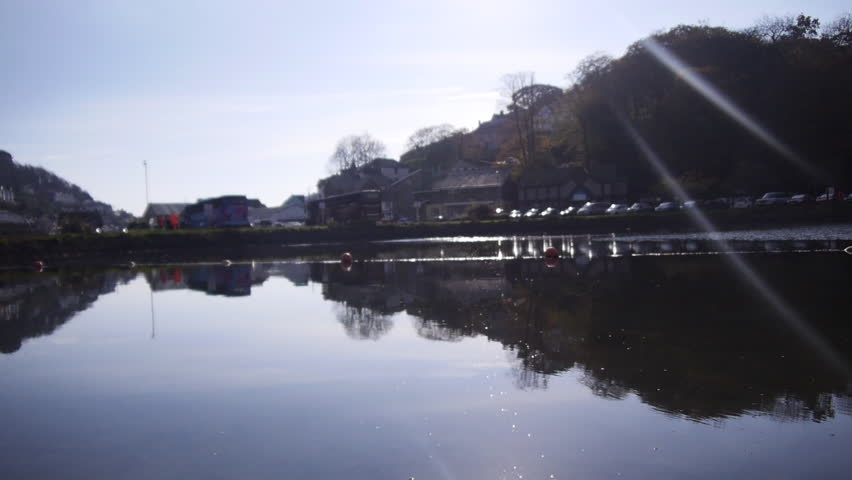 Looking across a mirror still section of the Millpool in West Looe, Cornwall, UK
