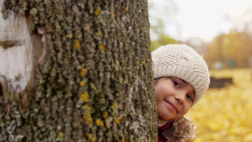Childhood, season and people concept - beautiful little girl hiding behind tree in autumn | Shutterstock HD Video #32419963