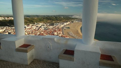 POV admiring Nazare skyline and beach waterfront from Miradouro do Suberco in Nazare Sitio, Central Portugal, Europe. touristic aerial view. Freedom and travel concept