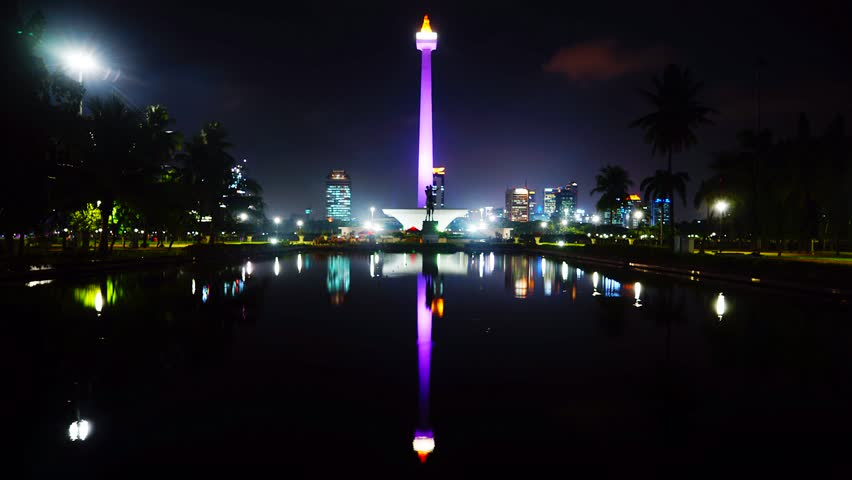 Timelapse of Monas or National Monument at night with reflection on the pool. A historical landmark placed in Jakarta, Indonesia.