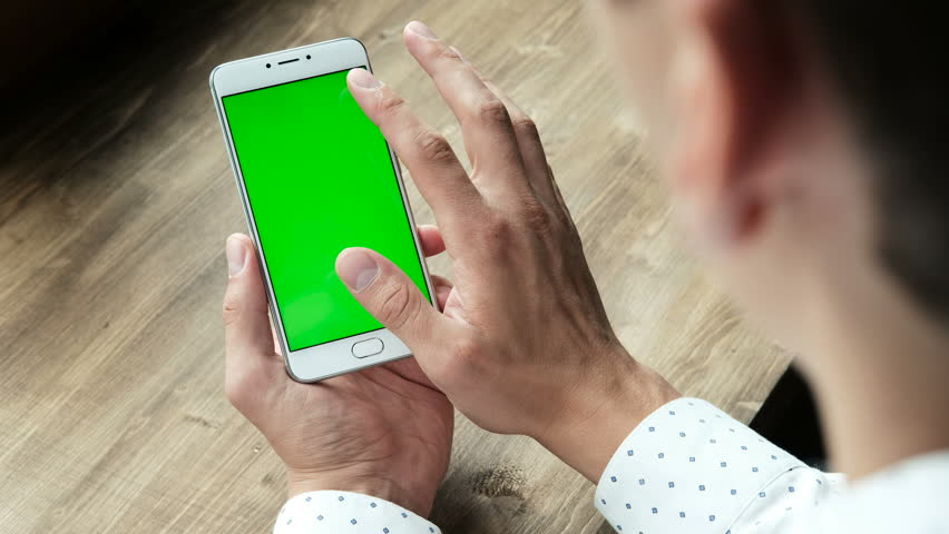 One modern businessman use the handheld cellphone with chromakey touchpad, gesturing closeup in workplace at wooden desk. Guy hold cellular portable device and tapping by surfing web point of view #32427613