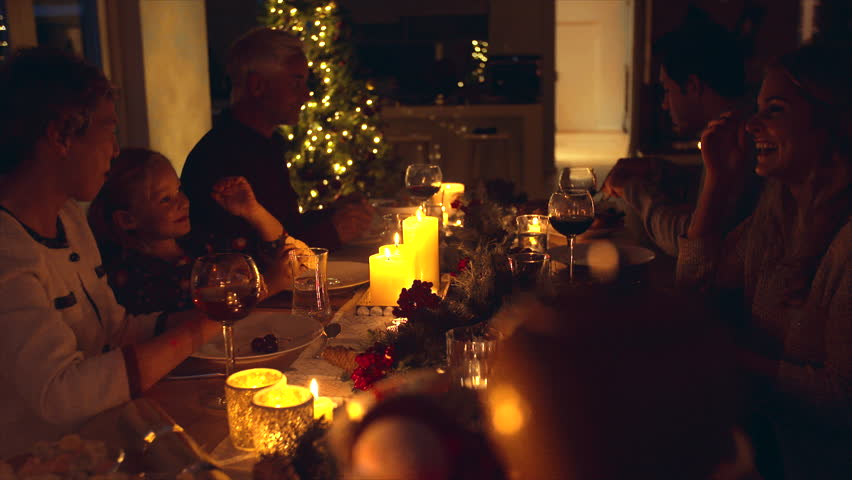 Extended family celebrating christmas together at home. Family of five sitting at dining table talking and having dinner together on Christmas eve.   Shutterstock HD Video #32437915