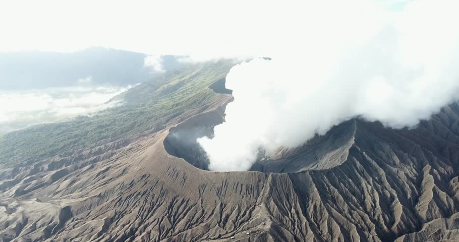 Aerial shot of Mountain Bromo active volcano crater in East Java, Indonesia. drone start in front of mountain bromo and fly to top view crater of mountain bromo.