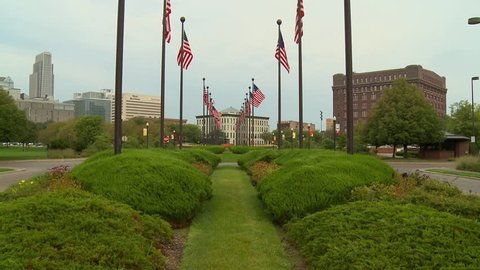 American flags wave in the wind in Omaha, Nebraska. It is morning in the garden with the sky line in the background. The building are old brick. Classic Midwestern Americana.