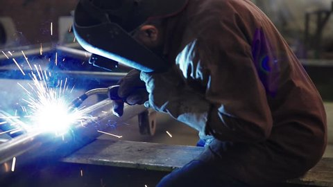 welder working and soldering iron with mask-slider shot