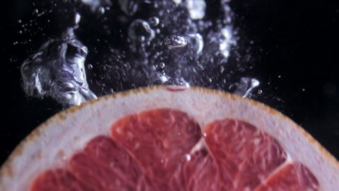 Round fresh juicy grapefruit slice plunging into transparent water with explosive stunning splash. Underwater high-speed slow motion shot on black background. Pomelo isolated.