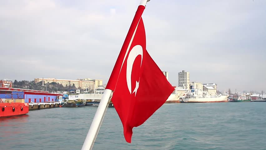 Seaport as seen from the waterside with a Turkish Flag waving. A tugboat moored in the background. Istanbul Haydarpasa Port has an open storage area of 350,000 m2 in Turkey.