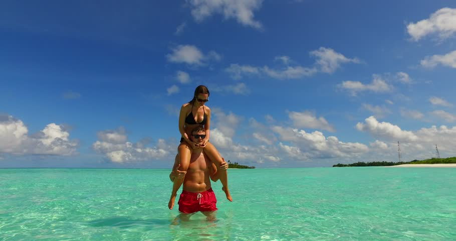 v15455 two 2 people together having fun man and woman together a romantic young couple sunbathing on a tropical island of white sand beach and blue sky and sea