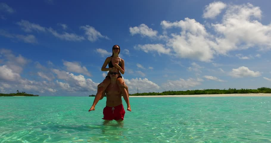v15465 two 2 people together having fun man and woman together a romantic young couple sunbathing on a tropical island of white sand beach and blue sky and sea