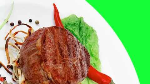 grilled beef fillet with thyme red hot chili pepper and tomato on plate over green screen slow motion hidef