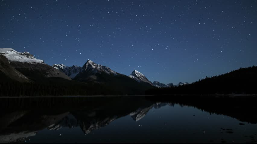 An night timelapse at Maligne Lake in Jasper National Park, Alberta, Canada. Reflections of shooting stars across the top of Leah, Samson Peaks and surrounding snowcapped mountains. A winter scene.