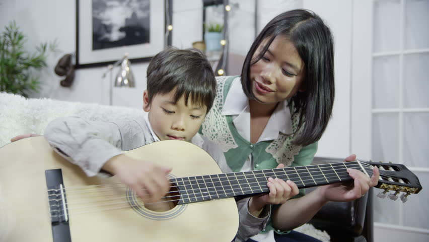 A mother gives her son a lesson in how to play the guitar