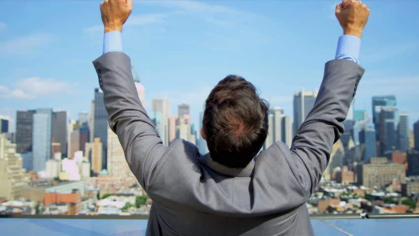 Hands up of Caucasian smart male celebrating business success on rooftop overlooking Manhattan shot on RED EPIC