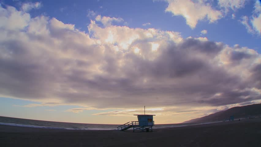 LOS ANGELES, CALIFORNIA, USA, 2012 Time lapse of a cloud formations moving behind a lifeguard station on a Los Angeles beach.