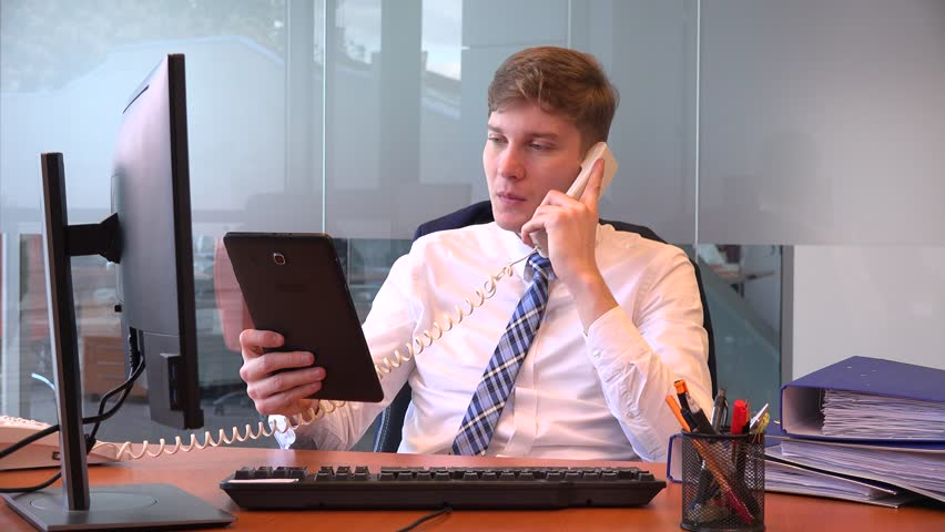 Adult smart business man in the office with tablet computer talking on telephone | Shutterstock HD Video #32567623