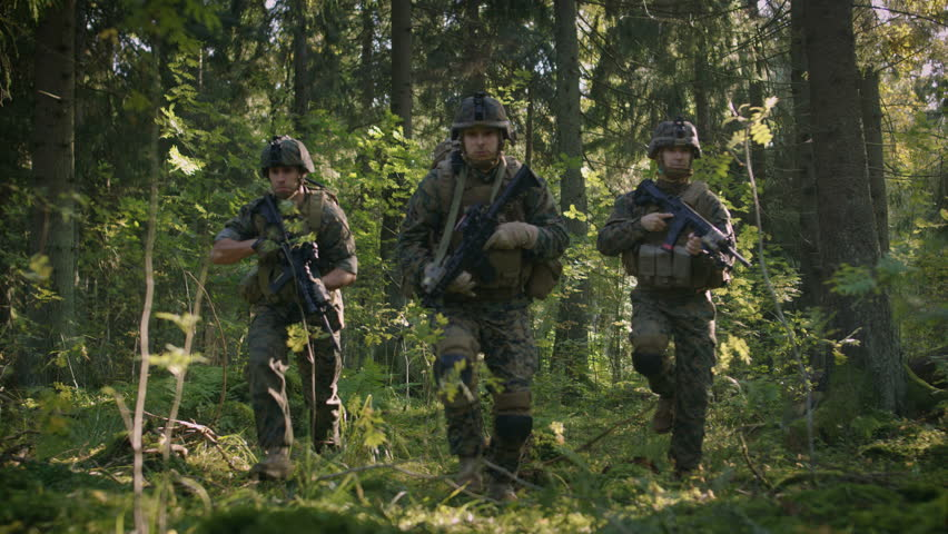 Three Fully Equipped Soldiers Wearing Camouflage Uniform Attacking Enemy, They're in Shooting Ready Stance, Aiming Rifles. Military Operation in Action, Squad Standing in Dense Forest. 4K UHD.