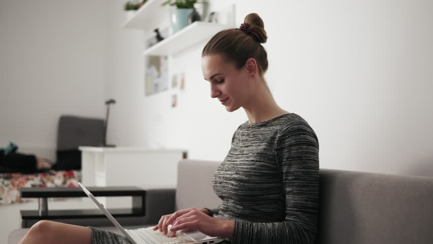 Side view of young woman at home sitting on the sofa, working with a laptop and typing text fast looking at the screen | Shutterstock HD Video #32588065