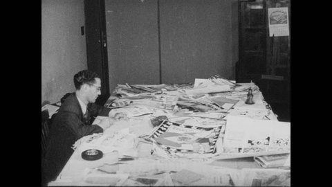 1940s: Men at desks reviewing artwork in Art Department. City desk with reporters smoking in their individual desks.