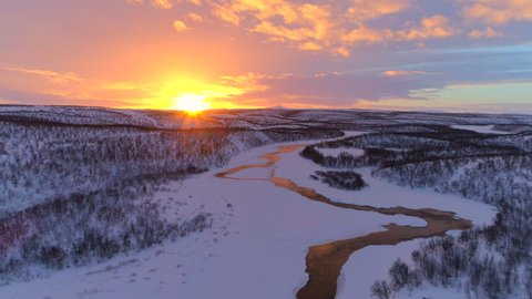 AERIAL: Flying above meandering river flowing through snowy winter wonderland in Lapland wilderness at dreamy sunset. Stream meandering through picturesque hilly countryside at golden sunrise, Finland