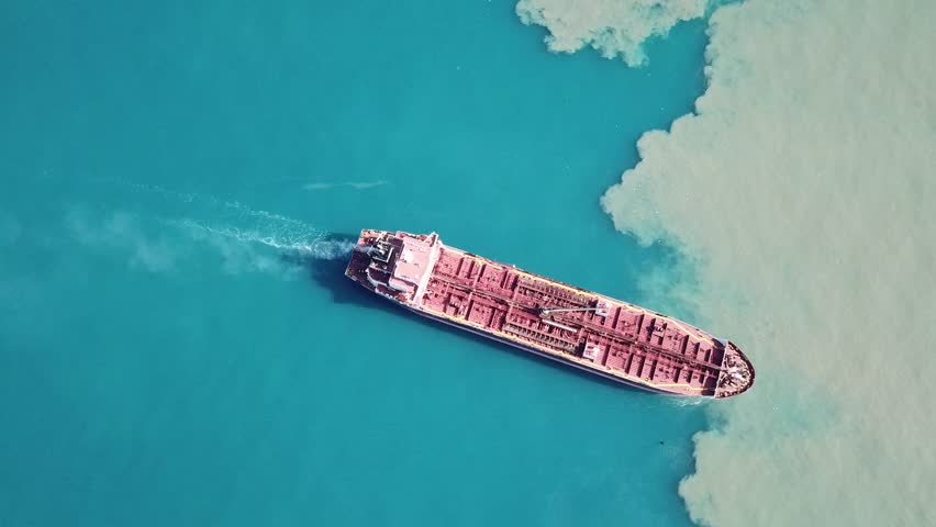 Dramatic Aerial top down shot of red deck tanker ship sailing on open sea with pollution