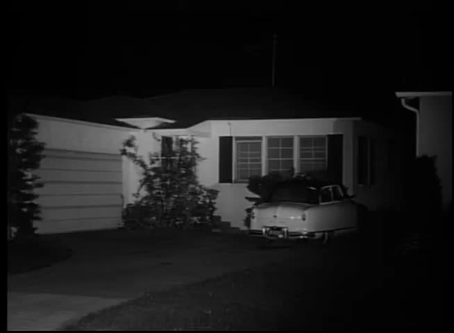 1950s Car Pulling Out Of Suburban Driveway At Night