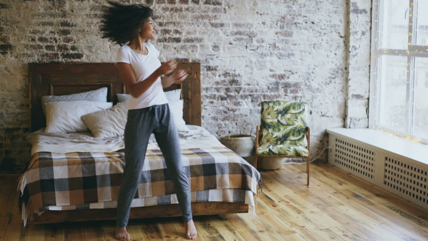 Attractive mixed race joyful girl have fun dancing near bed at modern apartment | Shutterstock HD Video #32672143