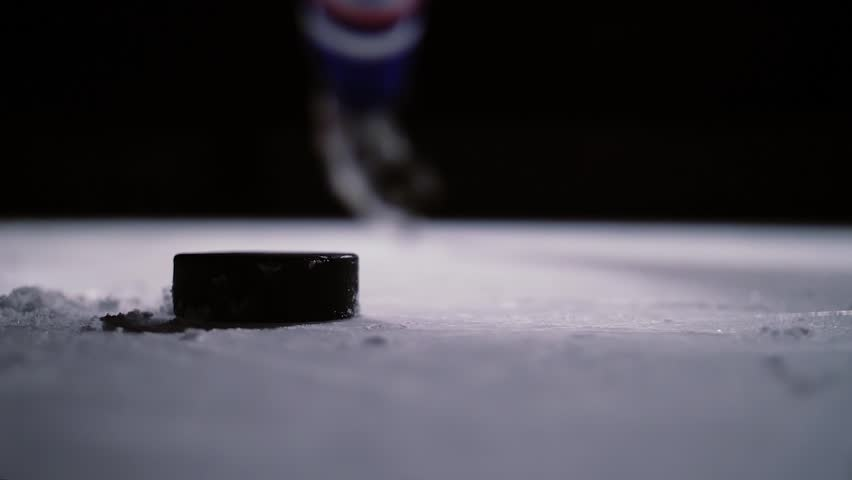 Professional hockey player produces a shot on goal at ice arena