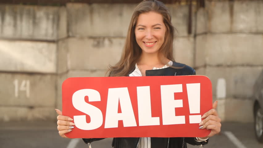 """The girl shows a sign """"SALE"""". 