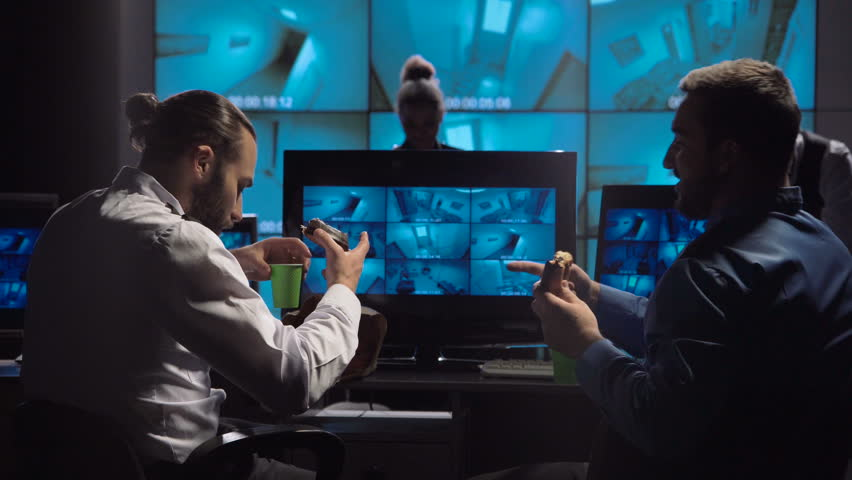 Two policemen eating doughnuts while working in room of video surveillance with monitors. | Shutterstock HD Video #32687233