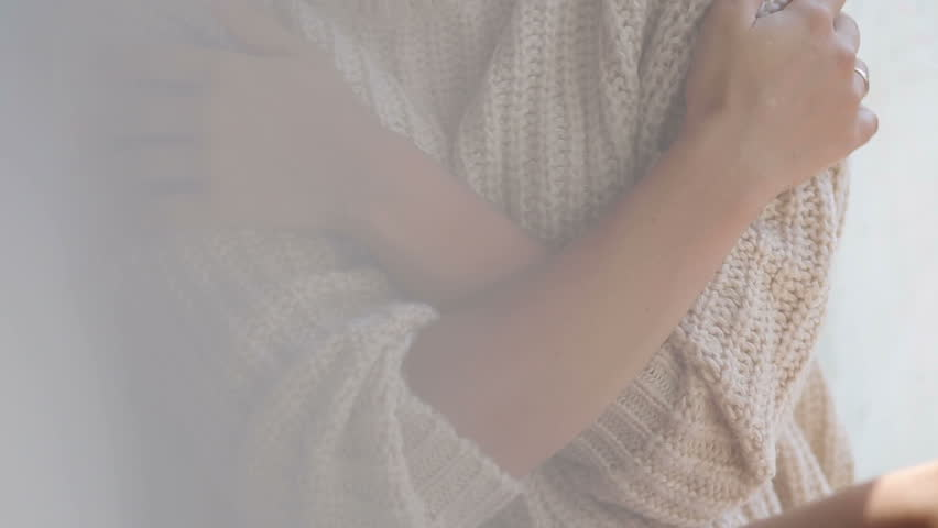 Girl in a knitted sweater and bare feet sitting on the window, close-up.