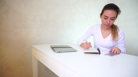 Young pretty woman making notes about income and expenses of family at end of month, and postpones money that was saved. Female sitting at the table, close laptop lies on it. Financial management