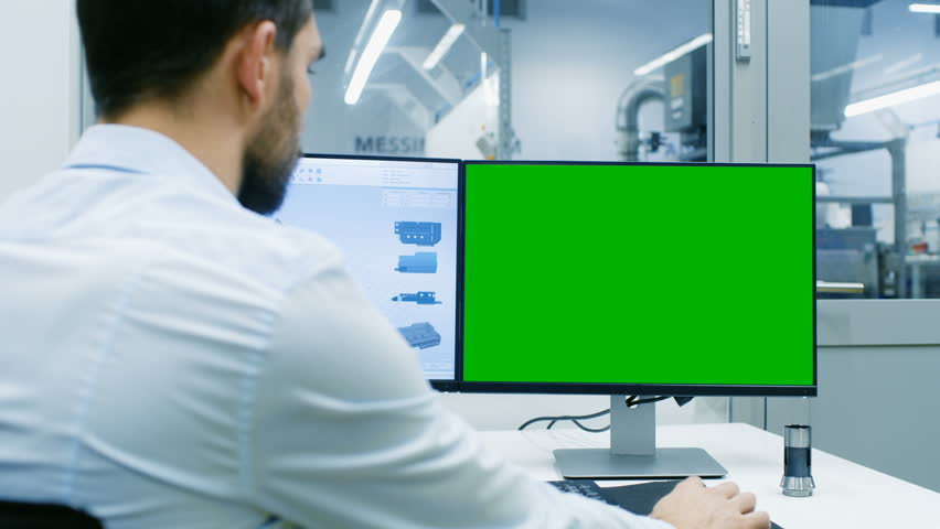 Engineer Working on a Personal Computer with Two Displays, He's Designing New Efficient Engine in CAD Program. Out of the Office Window Components Manufacturing Industrial Factory is Visible. | Shutterstock HD Video #32711848