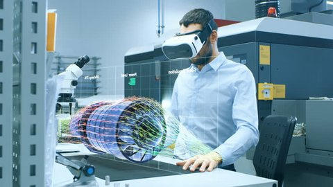 Factory Chief Engineer Wearing VR Headset Designs Engine Turbine on the Holographic Projection Table. Futuristic Design of Virtual Mixed Reality Application. Shot on RED EPIC-W 8K Helium Cinema Camera