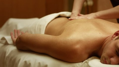 Shot of a professional masseuse massaging back and shoulders of a male client. Man receiving full body massage at spa relaxing rest wellness resort wellbeing pampering enjoying occupation service