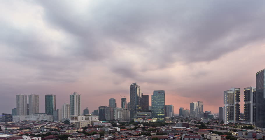 Sunset time lapse, as a day to night video with a pan to the left, over Jakarta skyline business district in Indonesia capital city. Jakarta is Indonesia capital and the largest city.