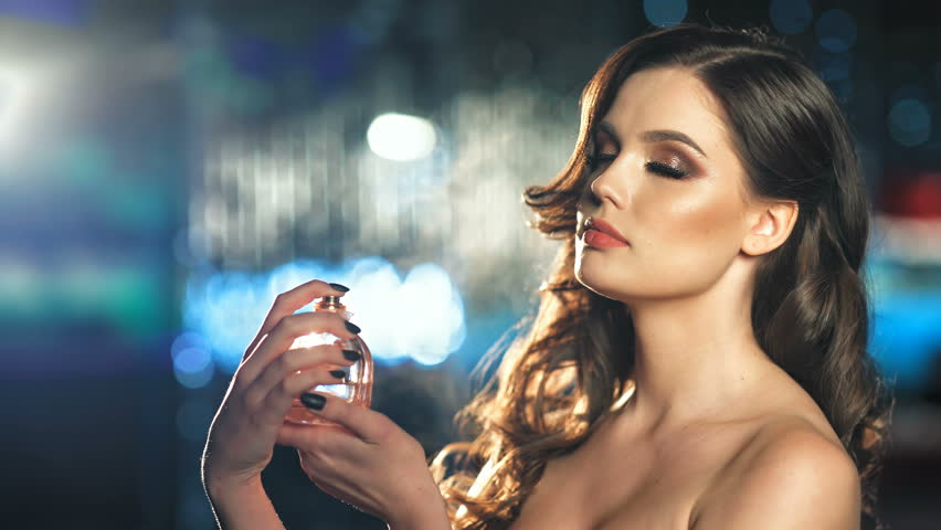 Beautiful fashion woman spraying perfume on her neck
