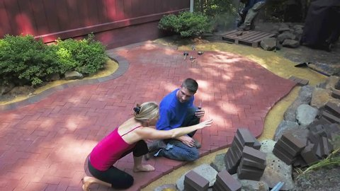 Aerial camera showing landscape architect going over the hardscaping project with a mature blonde woman client with bare