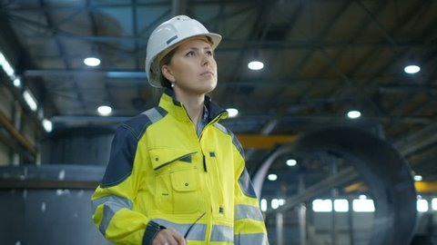 Female Industrial Worker in the Hard Hat Puts on Protective Goggles while Walking Through Heavy Industry Manufacturing Factory. In the Background Various Metalwork Components are Seen.