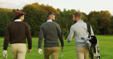 Three male friends with clubs and golf bag walking on the pitch. Back view