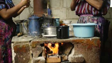 A pair of indigenous women dressed in traditional clothes make tortillas over a firewood kitchen in Guatemala.