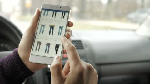 A man looks at the goods in the online clothing store, sitting in the car. Smart phone online shopping.
