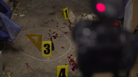 Knife bloody murder weapon detail. Part of a crime scene site at night collection. Forensic  police scientists working, looking for clues and evidence. Blood splatter analysis. In 4K, interior of a ho