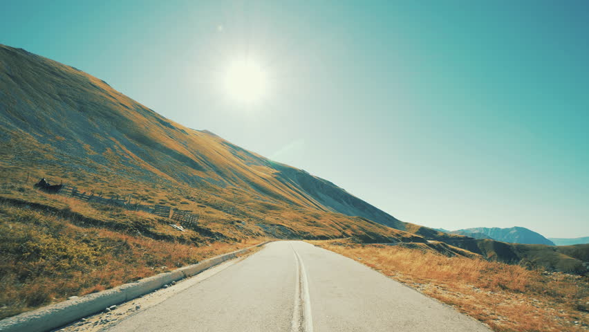 Driving On An Alpian-Like Sunny Mountain Pass Twisty Road.Pov drive on the winding roads of an Alpian mountain landscape on a sunny bright autumn day with the sun in view    Shutterstock HD Video #32874643