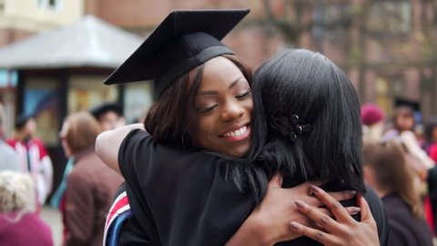 Graduation With Happy Black Graduate Female Hugged By Proud Mother. In Slow Motion.
