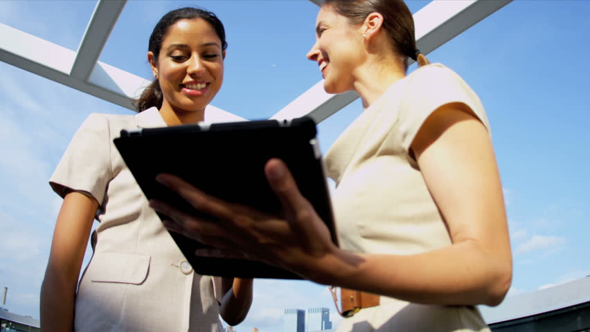 Multi ethnic ambitious businesswomen focusing online touch screen investment banking on city centre rooftop