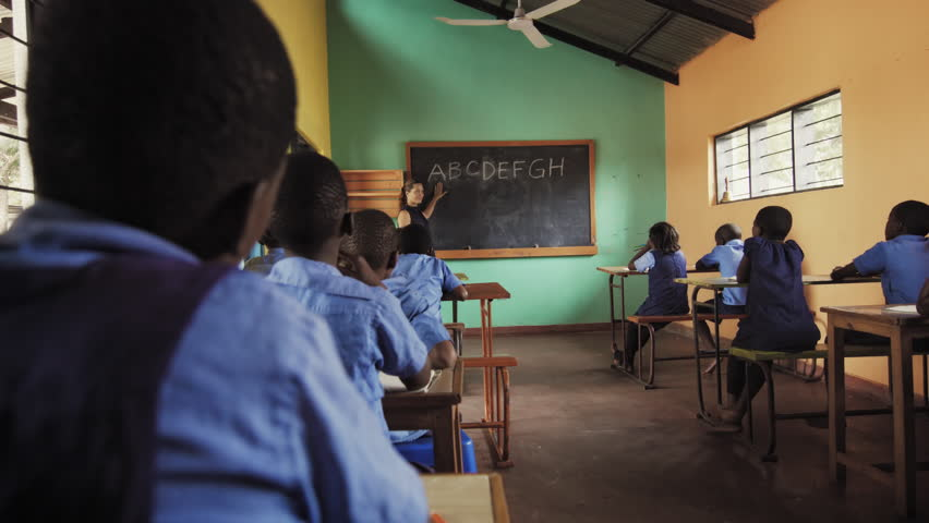4k back view of school classroom of African students learning english language alphabet off chalkboard.