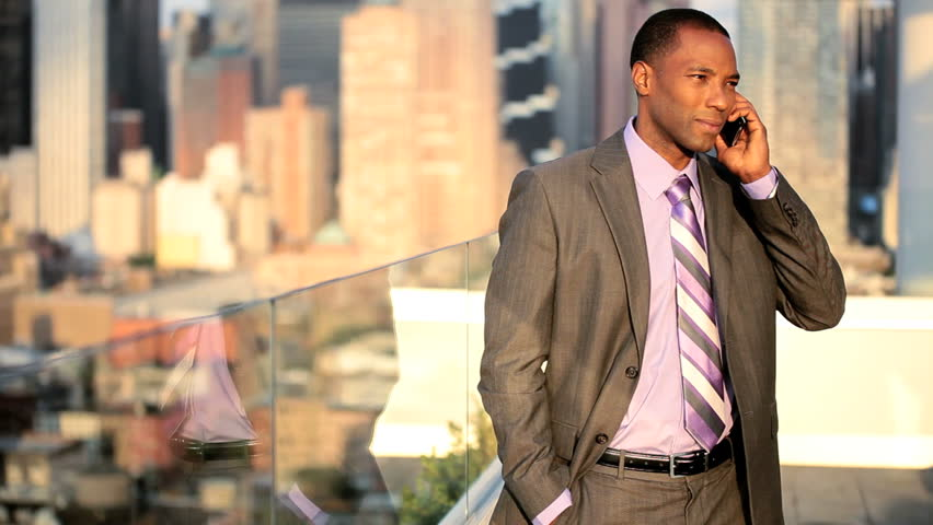 African American male business manager on a cell phone on rooftop overlooking the big apple