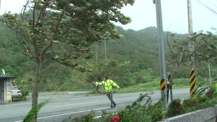 HUALIEN, TAIWAN - AUGUST 2009: Storm chaser measures strong winds as typhoon Morakot hits Taiwan.
