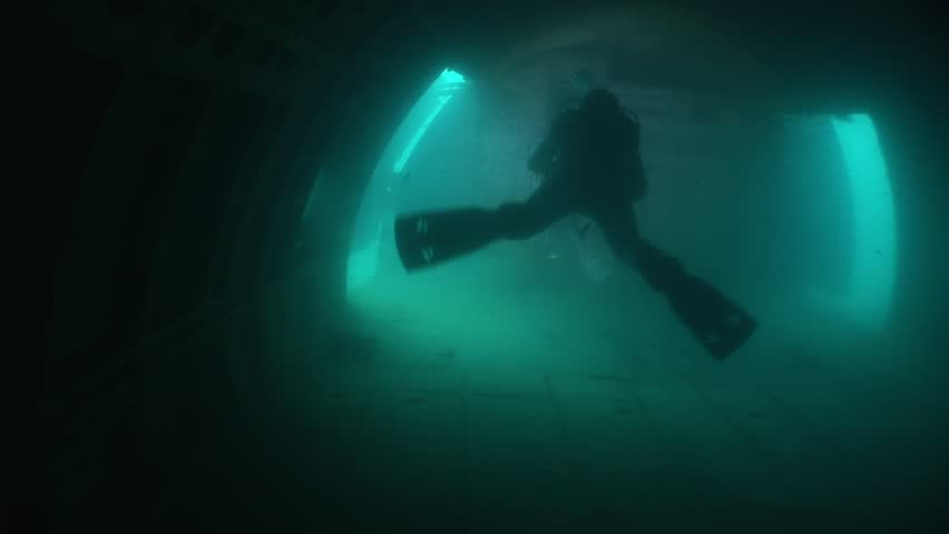 scuba diver exploring plane wreck underwater with a scooter